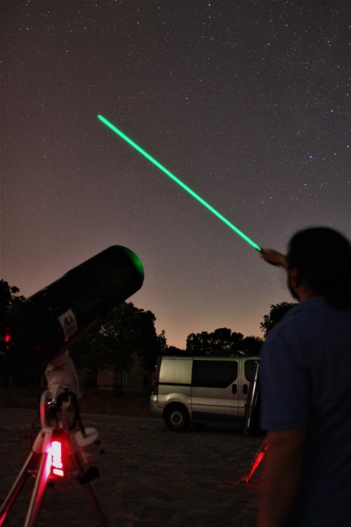 Tour por el cielo con un láser verde profesional en una observación astronómica